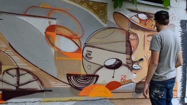 Umělec kreslí graffiti, obrázek osoby s dýmkou.