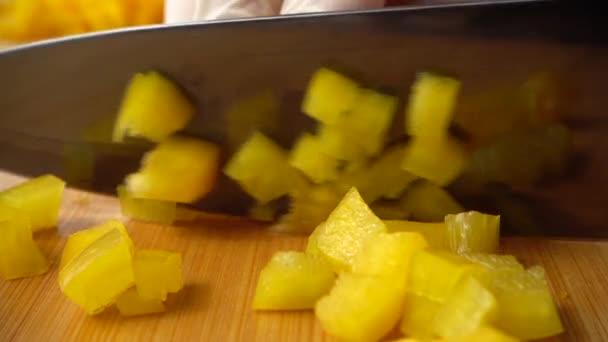 Kuchař krájí žlutý sladký pepř nožem. Zpomalený pohyb.