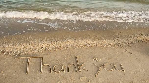 Danke handgeschrieben in Sand am Strand. Schießen am Strand.