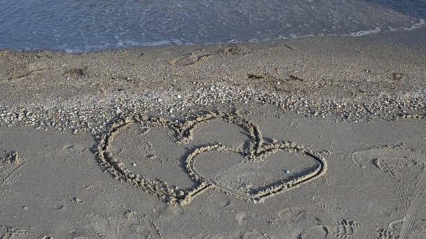 Dvě srdce na písku, pláž. Kreslení na písku.