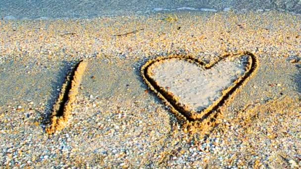 Inschrift auf Sand. Ich liebe. Schießen am Strand.