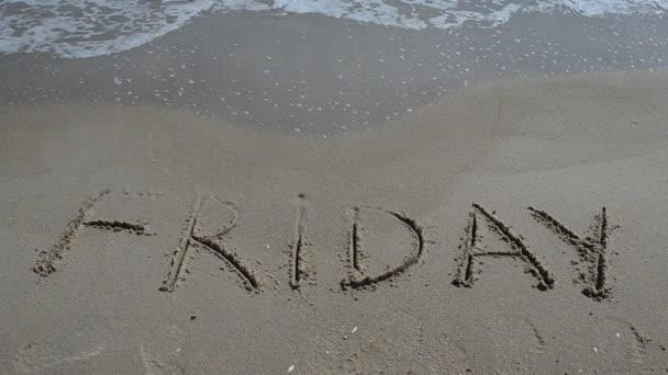 Felirat péntek egy szelíd homokos tengerparton a lágy hullám. Lövöldözés a parton.