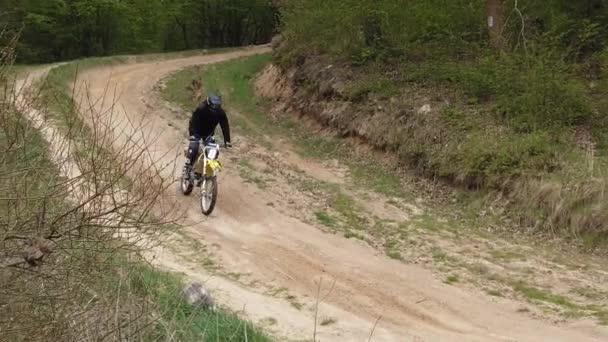 Neznámé motocykly vlak v hornatém terénu. Zpomalený pohyb.