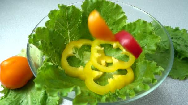 Padající rajčata na listech salátu. Zpomalený pohyb.