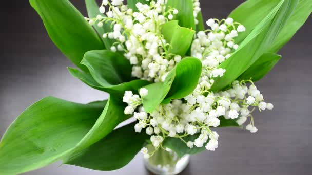 Lilies of the valley on a table. Flowers of lilies of the valley in a vase
