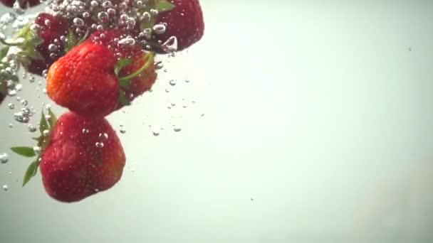 The falling strawberry in water. Slow motion.
