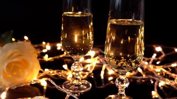 Sklenice na šampaňské a růže na pozadí jasných věnců.