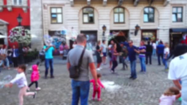 The man entertains children with soap bubbles in the city square. Out of focus.