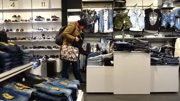 LA CORUNA, ŠPANĚLSKO - 1. dubna 2018: Neznámá žena si vybírá oblečení v obchodě. Nakupování v obchodě.