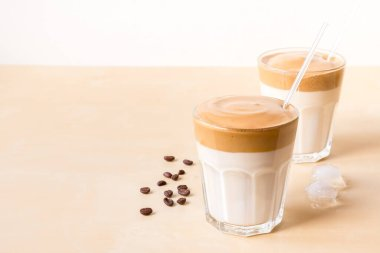 two transparent glasses of dalgon coffee on a wooden background.