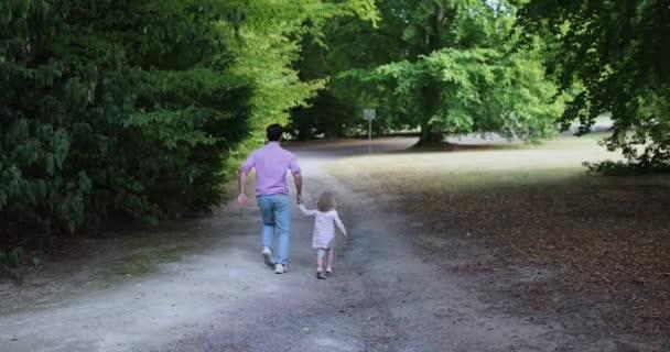Koncepce. Mladá matka a dítě dcera drží ruce a chůze