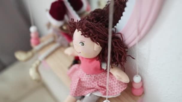 Malé panenky na polici se zrcadly v růžovém rámečku, vše na dívčích záchodech
