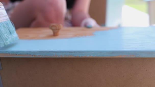 Schöne Blondine bemalt eine Holztür auf der Straße blau