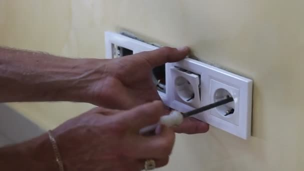 Elettricista che installa la nuova presa di corrente con cacciavite