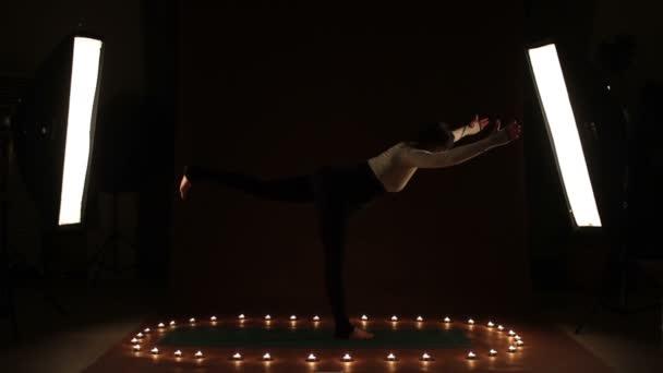Mladá žena ukazuje gymnastické cvičení ve tmě
