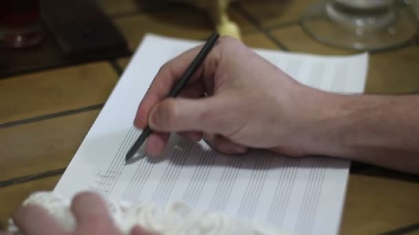 Hand pointing with pencil to music book with handwritten notes