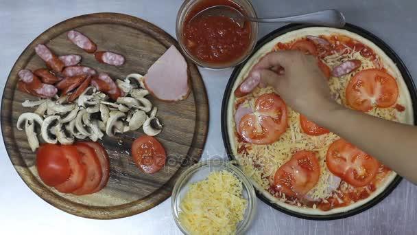 Kuchař připravuje pizzu. vrstva salámu. pohled shora