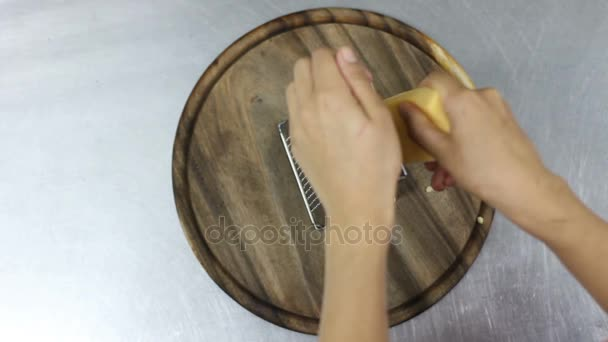 ženy ruční strouhání sýra s kovové struhadlo. pohled shora