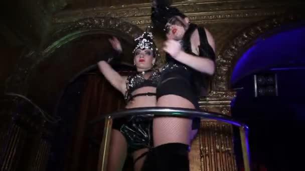 Frau in Bdsm Kostüm tanzen bei Discolights im Club auf Sockel