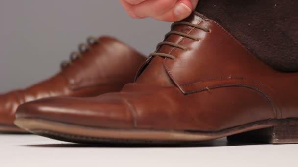 Mann trägt braune Schuhe. Seitenansicht