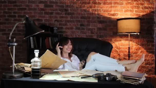 Krásná bruneta žena sedí v křesle s nohama na stole a poslouchejte hudbu na sluchátka