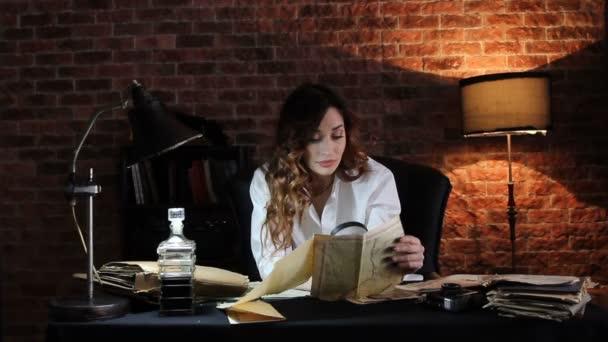junge brünette Frau im weißen Hemd im Büro betrachtet die Landkarte durch eine Lupe