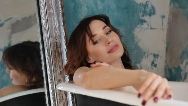 Hezká žena v koupelně tře olej v těle