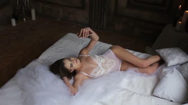 Sexy mladé ženy v posteli na sobě bílou kombinézu prádlo udělat selfie