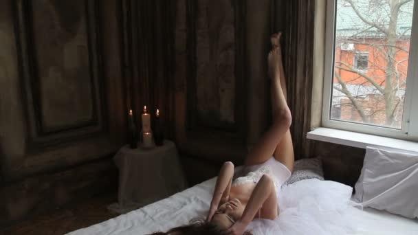 Hübsche sbrunette Modell trägt weißen Body im Bett mit hohen Beine