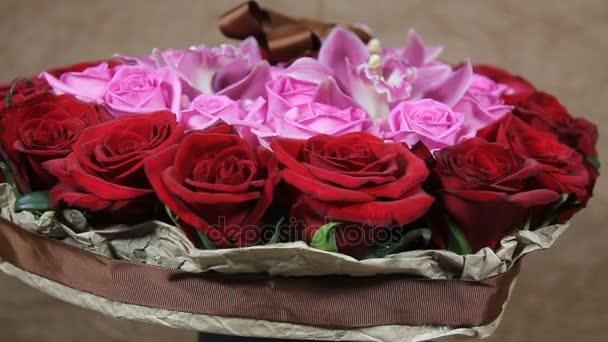 Červené růže a orchidej květiny kytice obraty