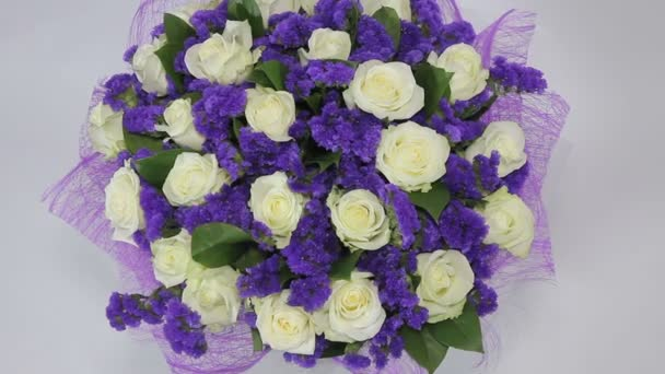 White roses flowers bouquet with violet decor turns. close up. top view