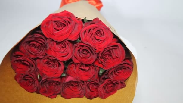 Red roses bouquet in paper package turns. close up