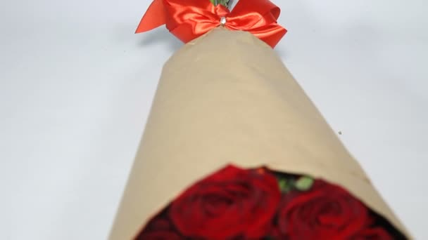 Red roses bouquet in paper package. rack focus