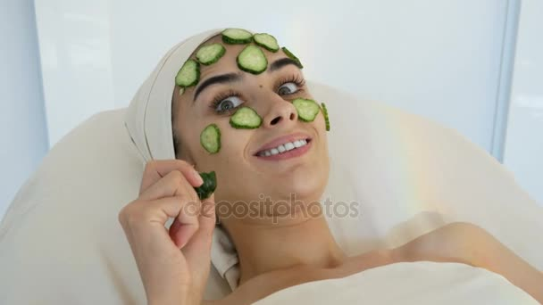 young and smiling women with cucumber mask at the beauty parlor eating cucumber