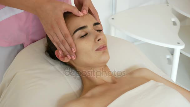cosmetologist do massage of womens forehead