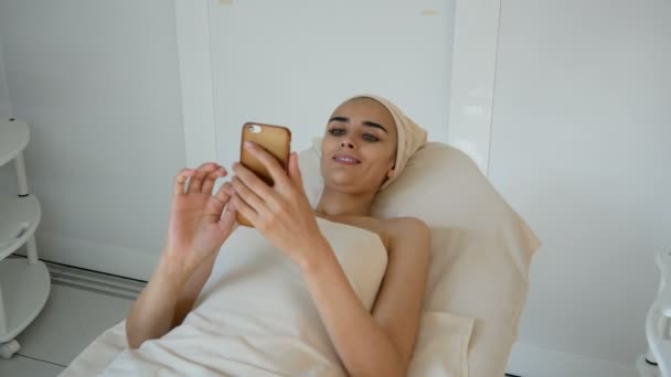 Beautiful women at the cosmetology procedures with phone in hands