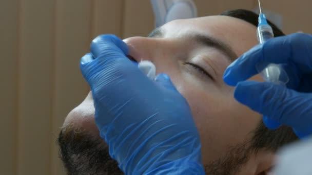 Filler injekce pro mužská tvář. Kosmetická chirurgie obličeje v beauty clinic. Ruku v lékařské rukavice s injekční stříkačkou píchne lék