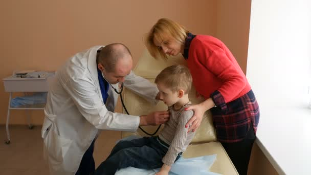 Child Patient Visiting Doctors Office with Mom. Pediatrician examining a little boy by stethoscope.