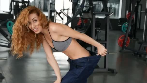 Žena ve své staré džíny po hubnutí. Sport a zdravotnictví koncepce