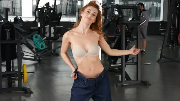 výsledek tréninku. Sport a zdravotnictví koncepce. ženy v posilovně představuje po hubnutí v její staré džíny větší velikosti