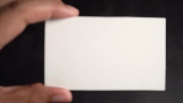 Kézfogás mockup fehér névjegykártya fekete alapon, nagyítás ki lassított felvétel.