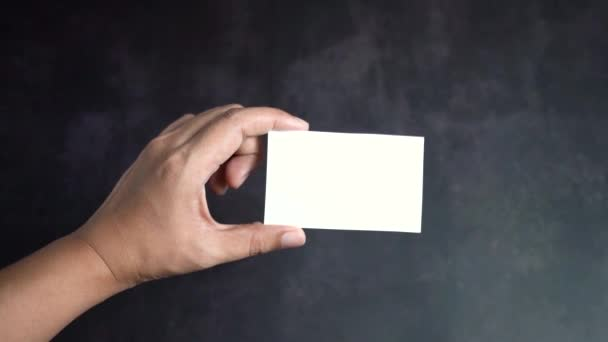 Hand holding mockup white business card on black background, Slow motion.