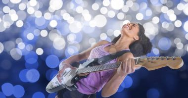 Happy female music artist playing guitar over bokeh