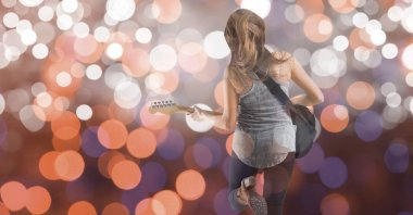 Rear view of music artist playing guitar over bokeh