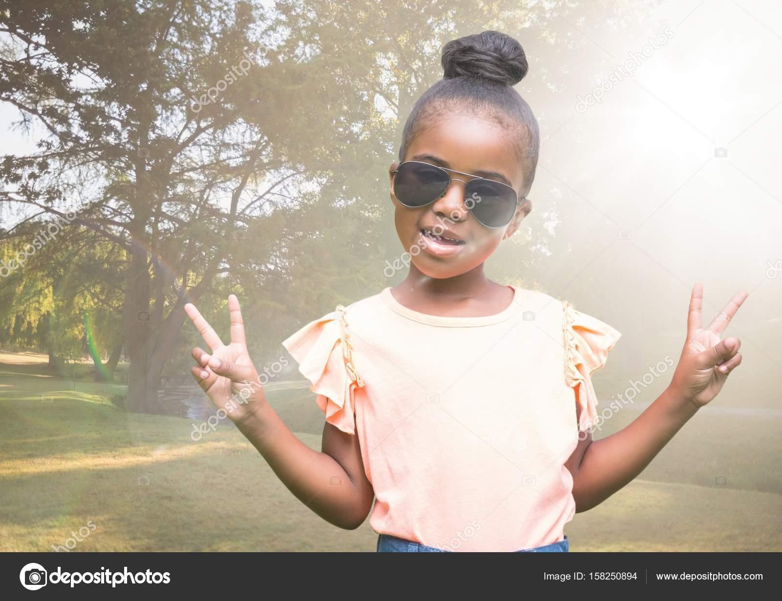 d8da9844562036 Digitale samengesteld van meisje in zonnebrillen maken van vrede tekenen  tegen wazig park met flare — Foto van ...