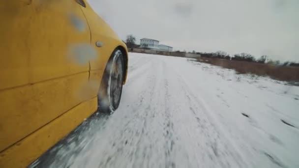 Nahaufnahme von gelbem Rallye-Auto, das im Schnee driftet