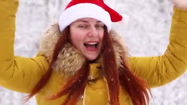 Vyhraj ten koncept. Mladá dívka v teplém zimním oblečení a vánoční klobouk vyskočí a cítí radostné emoce.