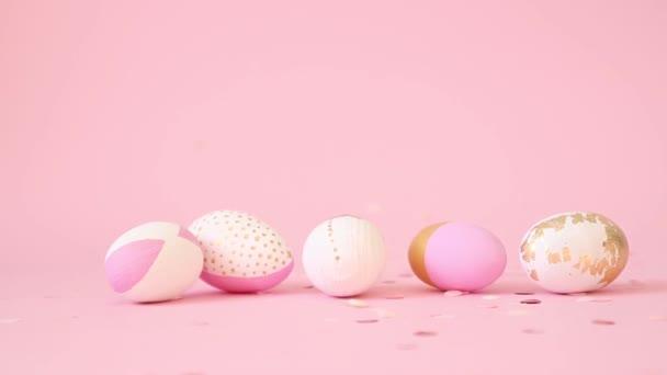 Růžové zlaté konfety kapky na zdobené vejce na růžovém pozadí. Minimální dovolená koncept. Velikonoční karta Swastika
