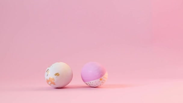 Happy Easter. Minimal concept with a golden egg pattern rolling over a pink background.