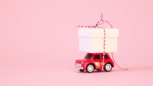 Červené retro autíčko dodávka dárková krabice s mašlí luk na růžovém pozadí. Narozeniny, Valentýn, Dámské den video koncept.